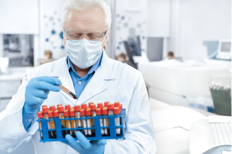 doctor in white lab coat holds rack of blood samples