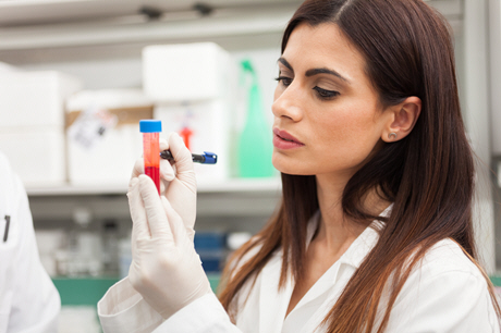 female doctor examines blood sample in lab