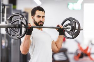 stock photo bearded muscular man wears white t shirt have workout with barbell in the gym 1057888280 300x200