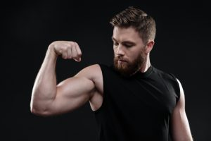 graphicstock fitness man demonstrates bicep looking at bicep in studio isolated dark background_S_2Fav2Snl 300x200