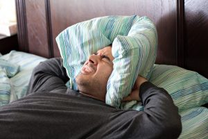 a man having trouble sleeping squeezes a pillow around his ears for some peace and quiet_Ht0bpVdASo1 300x200